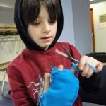 Eli makes himself fingerless gloves.