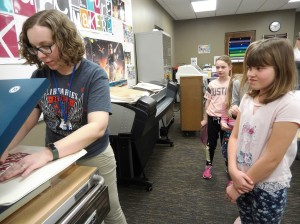 Kids use the heat press at The HUB's makerspace to make trendy tote bags.