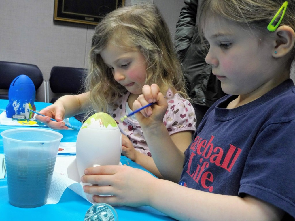 """Mercy and Brynn learn about budgeting with a craft at Mentor Public Library. The craft also offered a lesson in budgeting. The kids had to """"pay"""" for each paint color, forcing them to be frugal in their choices."""