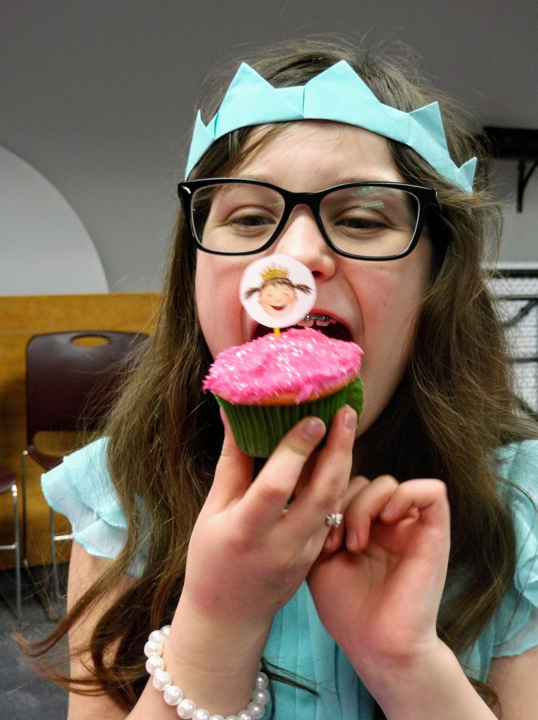 Hailey demonstrates proper form for noshing a cupcake.