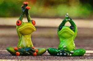 Two frog statues in yoga poses