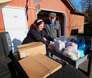Gail Borovic from Mentor Public Library helps unload Can Your Fines donations at the St. Gabriel Food Bank.
