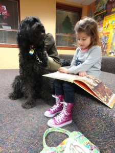 "Cara reads ""How do Dinosaurs Go to School?"" to Kody during Mentor Public Library's Paws to Read program."