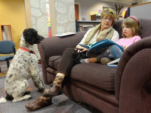 Ava practices reading with Toby, a standard poodle, and Janelle, Toby's owner.