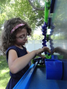 Lucy learns about friction and kinetic energy by playing with the magnetized marble slides at our summer reading kickoff party.