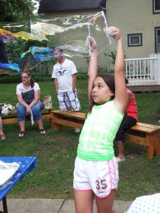 Lily uses a frame to make an enormous bubble during Mad Science Monday at Mentor Library