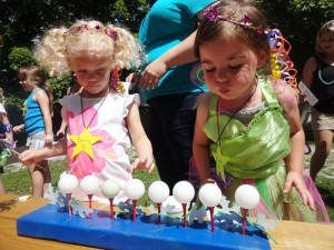Kacey and Emily practice blowing out birthday candles.