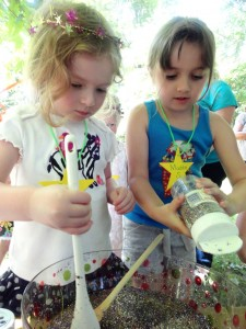 Evie and Maddie Smith pour glitter into a special Fairy Soup.