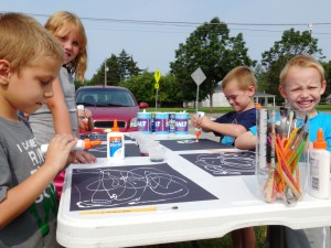 Kids use craft glue to make patters on their paper.