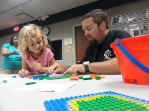 Ellie and Jason answer a math problem using Lego during the Family Lego Challenge.
