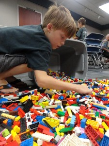 Alec searches for just the right Lego piece among the morass.