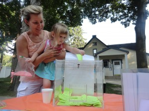 Lexi Neigoot (with a little help from Shana) puts a ticket in the case to win a second-chance raffle at our summer reading party.