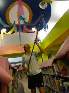Erin Sheplavy stretches to reach the framing around our carousel.
