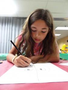 Abby draws Hula, a superhero she created.