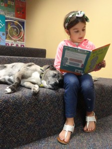 "Cara reads ""We Are in a Book"" to Fragg during the most recent session of Paws to Read."