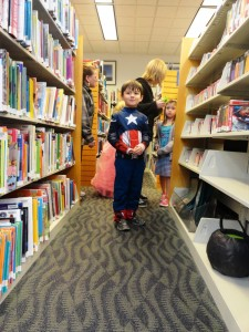 Luke searches the bookshelves of our Lake Branch for the next clue.