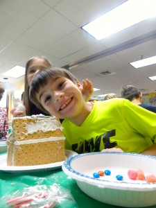 Jaydon simultaneously smiles, shows off his graham-cracker house and blocks his younger sister out of the frame.