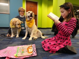 Taylor reads to a pair of therapy dogs—Honey (on the left) and Hannah—during Paws to Read at Mentor Library.