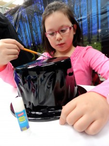 Lilly paints her top hat. (The Mad Hatter would be impressed.)