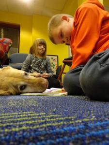 Jake and Claire take turns reading to Jazzy during Paws to Read at Mentor Library.