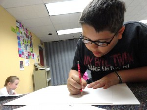 """Colin Weiss starts sketching his superhero for MPL's """"Every Hero Has a Story"""" summer reading program."""