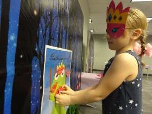Natalie tries to plant a lip print on the frog while blindfolded.