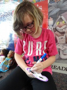 Addie draws rings of blue and purple around her Mardi Gras mask.
