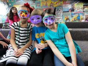 Eva, Claire and Sabrina show off the Mardi Gras masks they made at Mentor Library.