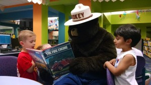 Now, it's Smokey's turn to read to the kids... or, at least, show them the pictures.