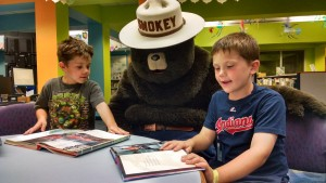 Kids read to Smokey the Bear when Smokey and his friends from Mentor Fire Department visited on Thursday.