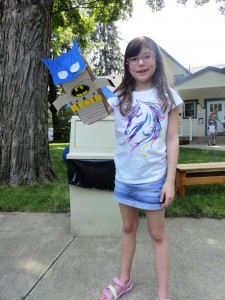 Rowan shows off the Batman paper puppet she made.