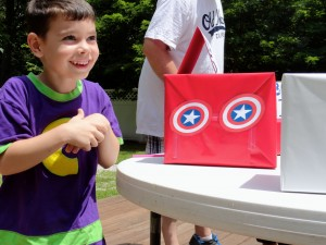 Colton grins while completing Captain America's intelligence test. Kids had to figure out what each box concealed.