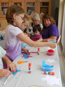 Kids celebrated the Fourth of July with patriotic crafts, including red, white and blue pencil wands.
