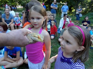 Emma and Sophia pet the bearded dragon from Herps Alive, a rescue refuge for reptiles.