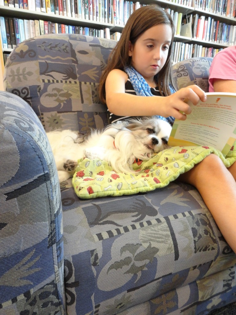 Caesar relaxes while Maria reads to him.