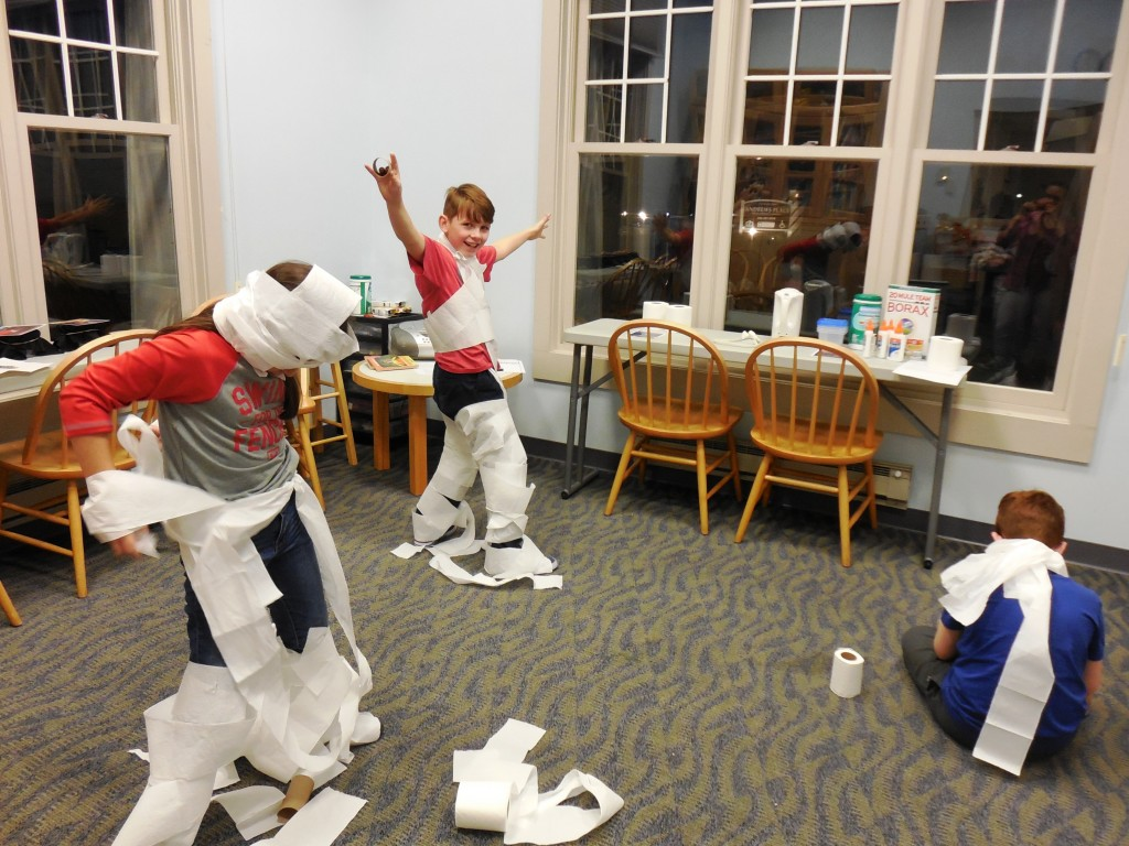 The kids race to see who can turn themselves into a mummy quickest during the Goosebumps Party at MPL's Lake Branch.