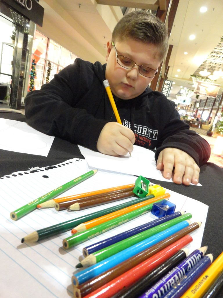 Tristan sketches his comic before adding details with the colored pencils.