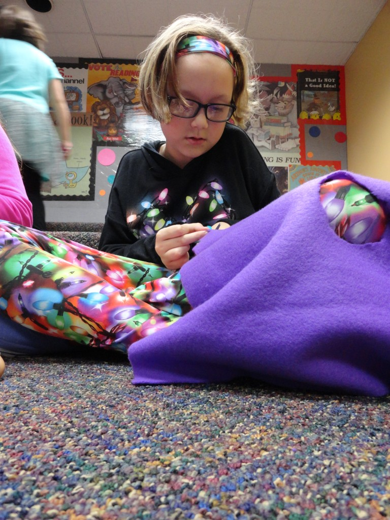 Addie makes a poncho for her doll during the American Girl Book Club meeting.