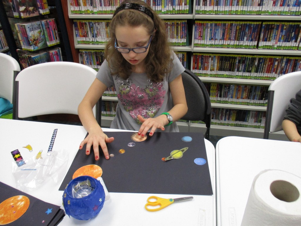 Cheyenne puts the finishing touches on her solar system.