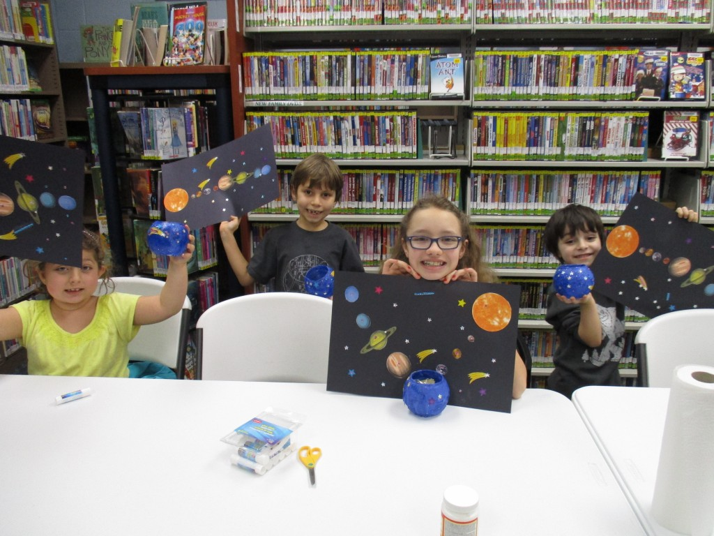 Kids show off the solar systems they created during the Passport to the Stars programs