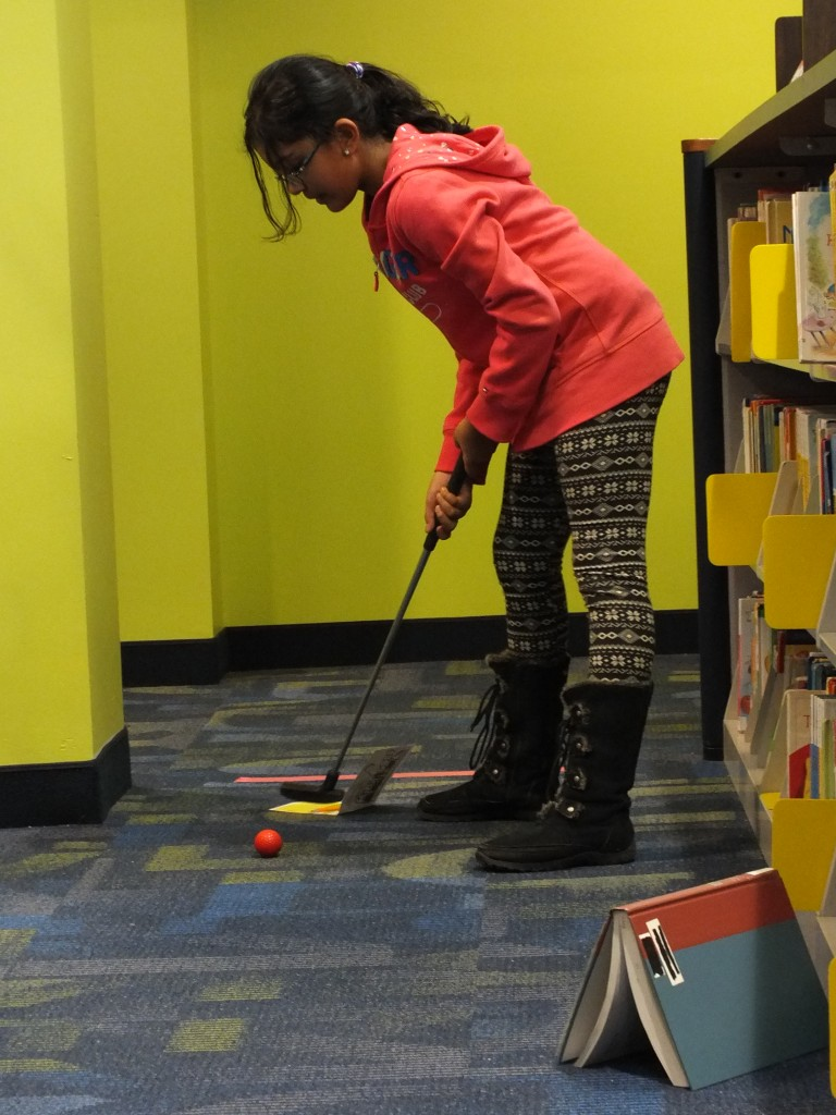Rhea putts in the Brazil-themed hole.