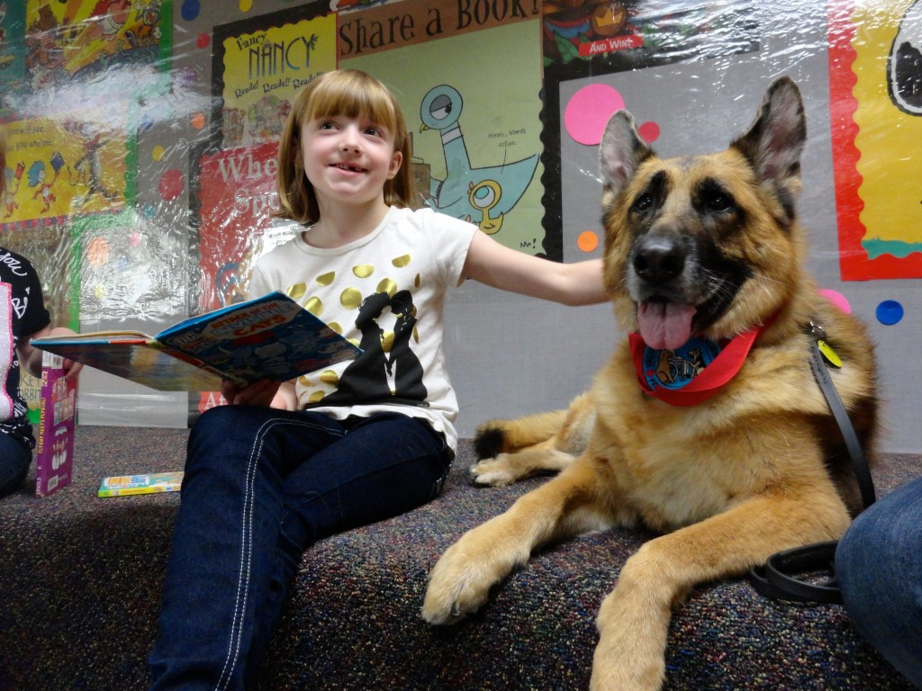 Claire takes a quick break to give Diva a scratch behind the ears during Paws to Read at Mentor Public Library.