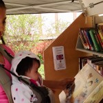 Catalea and her mother enjoy an impromptu story time by the Pop-Up Library during an Earth Day Celebration at Wildwood Cultural Center in Mentor.