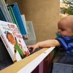 A toddler reaches for a book on the Pop-Up Library during the CityFest celebration in Mentor.
