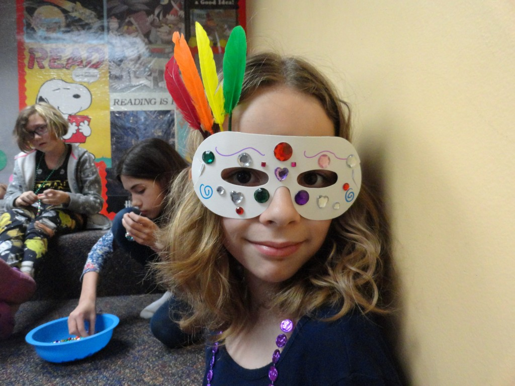 Sarah decorates her Mardi Gras mask with colored feathers and beads.