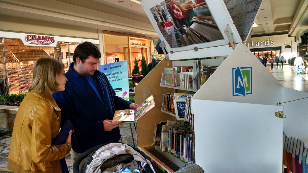 A family glances at the books in the Pop-Up Library while shopping at Great Lakes Mall.