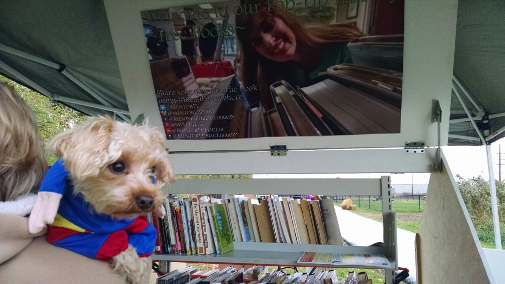 A pet owner peeks at the Pop-Up Library during the annual Howl-O-Ween party at Mentor Dog Park.