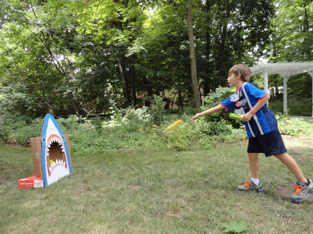 Avery tosses fuits and veggies into the gaping maw of our shark during a nutrition-themed Move-It Monday.