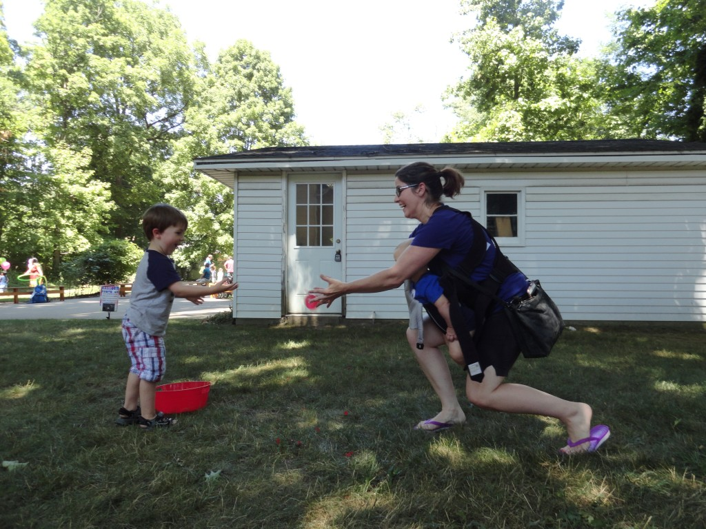 This photo is, itself, a metaphor for parenting. A mom plays water-balloon catch with one child while carrying another.