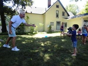 Luke and his grandpa play catch with a water balloon in our backyard.
